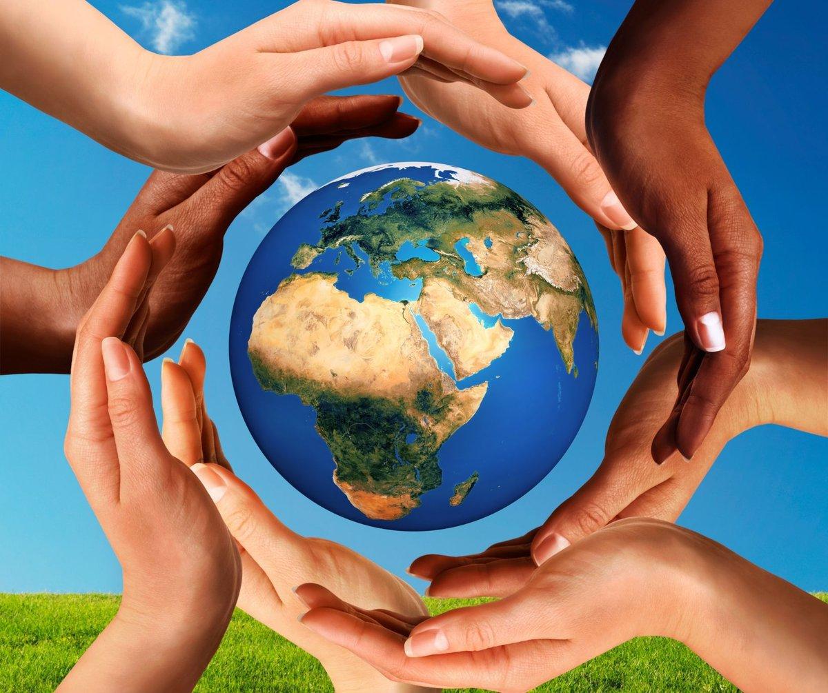 children's hands around an image of the world